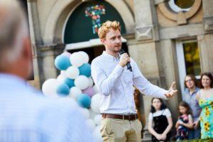 Adam Kucharski stands giving a speech