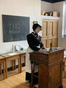 Image of Matron - dressed in a black Victorian style dress, apron and bonnet, in a Victorian classroom.